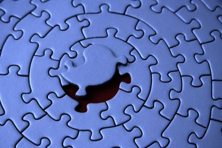 fitting in: blue jigsaw with the missing piece laying above the space - pieces fitting together in form of a spiral Stock Photo