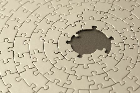 jigsaw in sepia with missing pieces in the center - shallow DOF, focus is on the big hole Stock Photo
