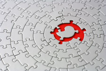 grey jigsaw with space and one of the missing pieces in the red center - pieces fitting together in form of a spiral Stock Photo - 1787207