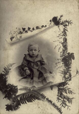 ancient photo of a child posing in its christening robe - from 1902 - with scratches