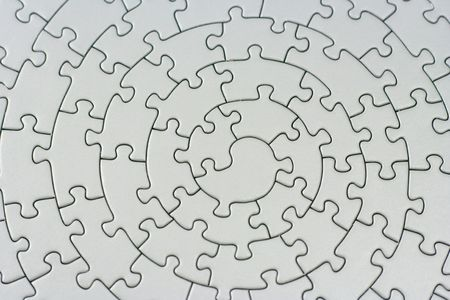 complete grey jigsaw - pieces fitting together in form of a spiral -