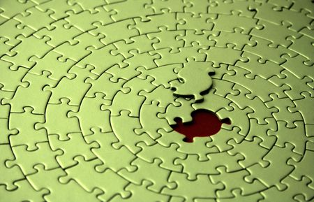 shallow dof: green jigsaw with the missing piece laying above the space - shallow DOF, focus is on the missing piece -