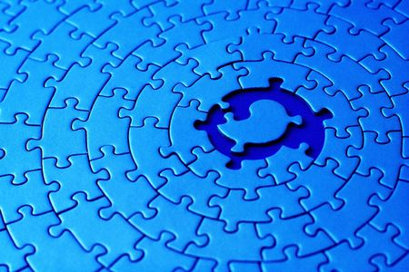 abstract of a blue jigsaw with space and one of the missing pieces in the center - pieces fitting together in form of a spiral -  photo