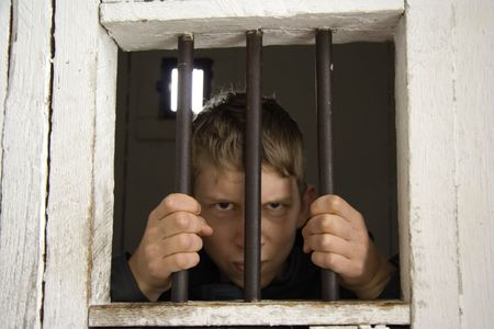 rowdy behind ancient prison bars - focus is on the hands - Stock Photo - 1807593