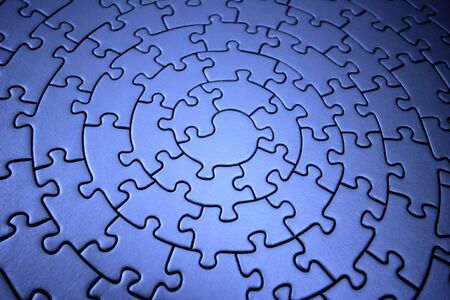 puzzle shape: three-dimensional blue jigsaw - wide angle, shallow DOF, focus is on the piece in the center - Stock Photo