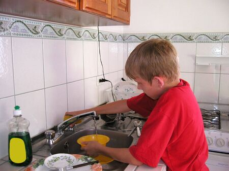 wash dishes: boy doing the dishes Stock Photo