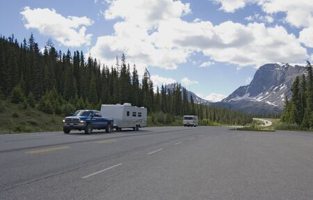 pickup with trailer having a good trip in the rockies - icefield parkway, banff national park, canada