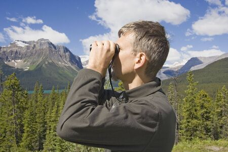 park ranger in the rockies, canada - with his field glass -