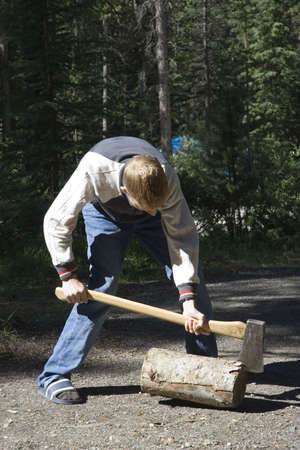 teen with an axe - chopping wood on a campground in canada -  photo