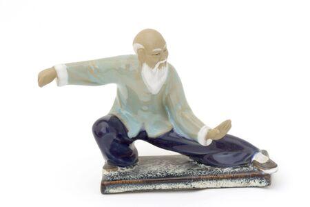 chi: senior practising tai chi - figurine over white - Stock Photo