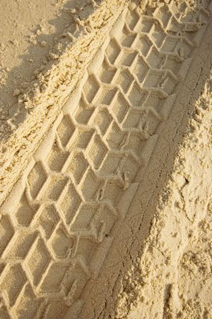 skidmarks: tracks on a sandy beach - closeup - in warm sunlight -