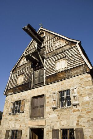brewage: an ancient brewery with wooden shingles - against a blue sky Stock Photo
