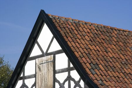gable house: gable of a half-timbered house in black and white with red tiles - in a traditional german village Stock Photo
