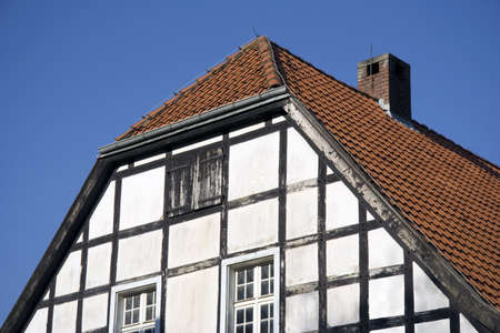 closeup of a half-timbered house in black and white with red tiles - in front of a forest in autum colors Stock Photo