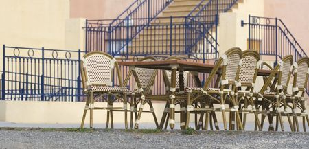 pavement cafe in front of stairs - tables and cane chairs photo