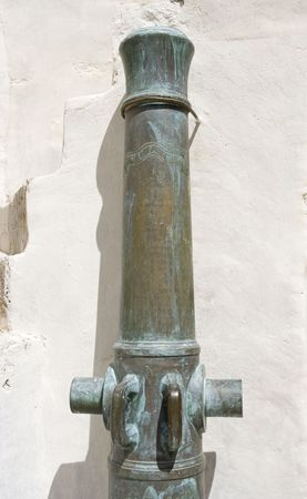 gunmetal: cannon in front of a white wall - cast-bronze 1787 in sevilla, spain