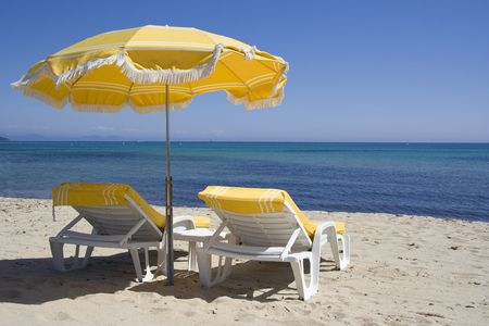 lounge chairs and parasol on the beach of saint-tropez - summer on the french riviera