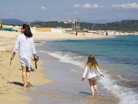 mother and daughter walking at the beach - saint-tropez, french riviera