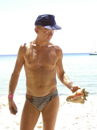 swimming trunks: man holding a tropical seashell - tobago, west indies Stock Photo
