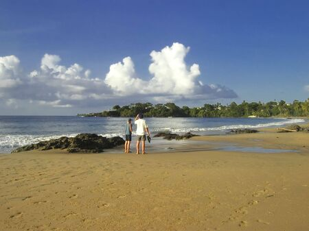 tropical beach with father and son - sunset on tobago, west indies photo
