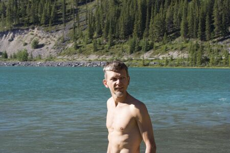 hardy: mature man in a cold lake with a water temperature about 5&deg,C or 40&deg,F - waterfowl lake, banff national park, canada