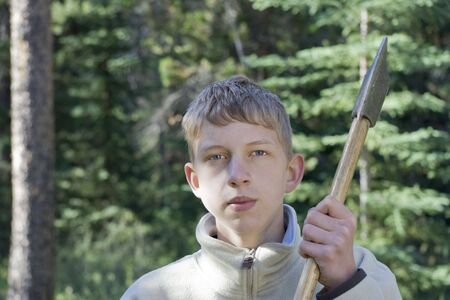 bore: teenage boy holding an axe - wood-chopping in jasper national park, canadian rockies