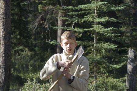 teenage boy holding an axe - wood-chopping in jasper national park, canadian rockies photo