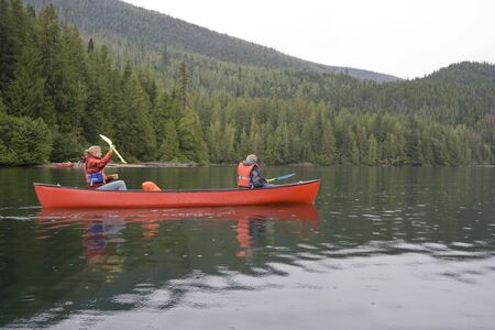 Girl and boy canoeing - Clearwater Lake, Wells Gray Provincial Park, British Columbia, Canada photo