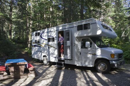 wooded: Big Motorhome at a wooded campground with young woman - Highway 18 in British Columbia, Canada Stock Photo