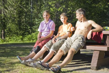 Happy family on bench - Wells Gray Provincial Park, British Columbia, Canada photo