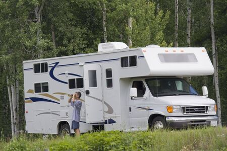 Big Motorhome with owner in the woods - Wells Gray Provincial Park, British Columbia, Canada Stock Photo