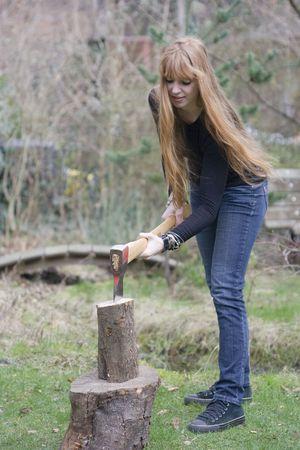 umschwung: Junge Frau hackt Brennholz - in den Garten