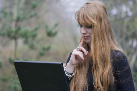 Pensive Young Woman using Laptop - outdoors photo