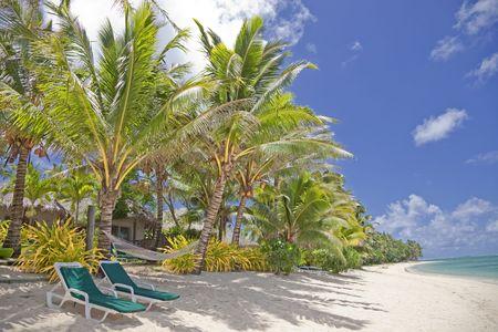 rarotonga: Spiaggia tropicale con palme, sedie a sdraio e Palm-thatched Rifugi - Rarotonga, nelle Isole Cook, Polinesia