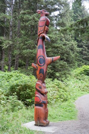 Totem Pole in the Woods - Pacific Rim National Park, Vancouver Island, British Columbia, Canada - Totem Pole of the Ucluelet First Nation on the South Beach Trail with a thunderbird, killer whale, bear and a salmon photo