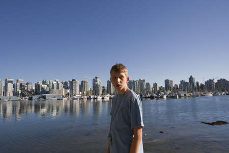 Teenage Boy in front of City Skyline - Vancouver, British Columbia, Canada photo