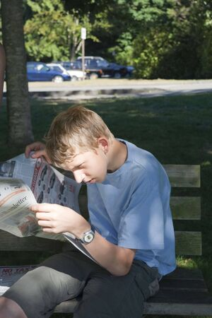 Teenage Boy reading Newspaper - Vancouver, British Columbia, Canada photo