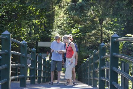 Family looking into a Map - Footbridge in Stanley Park, Vancouver, British Columbia, Canada Stock Photo