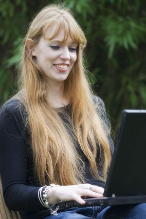 Young Woman typing on a Laptop - outdoors Stock Photo