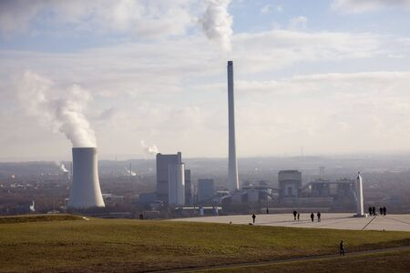 People on a Heap with Air Pollution in the Background - Halde Hoheward, Herten, North Rhine-Westphalia, Germany, Europe Stock Photo