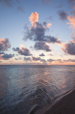 Sun setting behind Cumulus Clouds over Ocean and Island - Rarotonga, Cook Islands, Polynesia Stock Photo