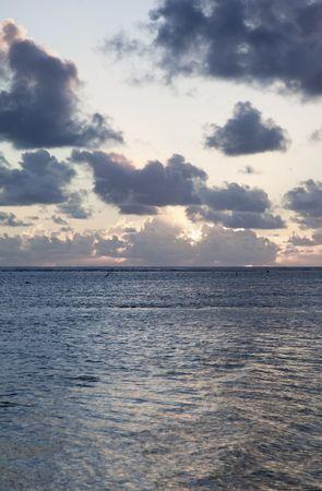 Sun sinks to Sea under a cloud-filled Sky at Sunset - Rarotonga, Cook Islands, Polynesia
