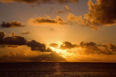 Sunrays from behind gray Clouds above South Pacific Ocean - Rarotonga, Cook Islands, Polynesia Stock Photo