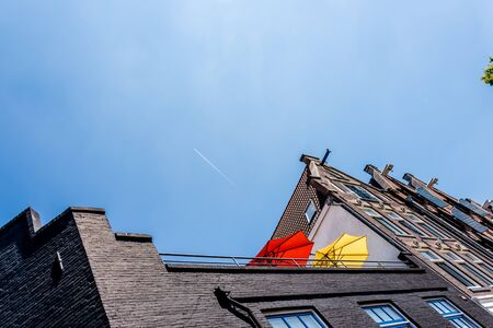 red and yellow parasols on a high balcony against blue sky and an airplane flying over real high