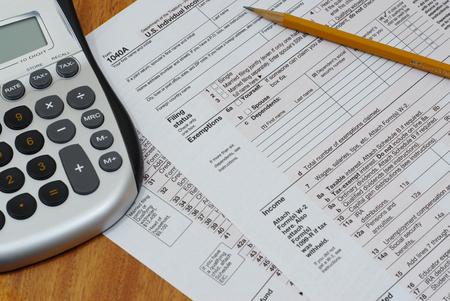 internal revenue service: Close up detail of US Internal Revenue Service tax form with pencil and calculator