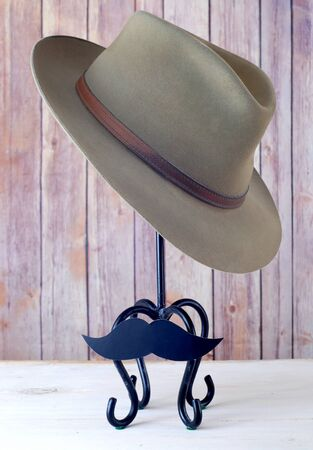 Old mens hat on hat stand with mustache in front of wooden background for Mens Health Awareness month in November