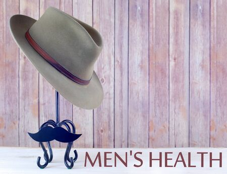 Old mens hat on hat stand with mustache in front of wooden background for Mens Health Awareness month in November.