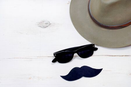 health awareness: Old mans hat with sunglass and a mustache on rustic wooden background for Mens Health Awareness month in November.