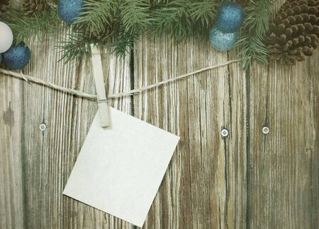 Blank message card hanging from twine with a clothespin on rustic wooden background with vintage filter applied. Upper border of evergreen, pinecones and Christmas decorations