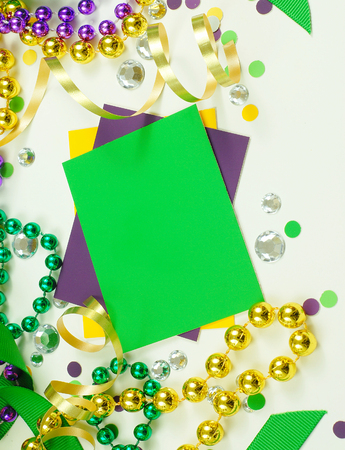 carnivale: Green, gold and purple Mardi Gras image with three color cards, ribbons, beads and confetti. The cards are blank with copy space for your image. Vertical composition.